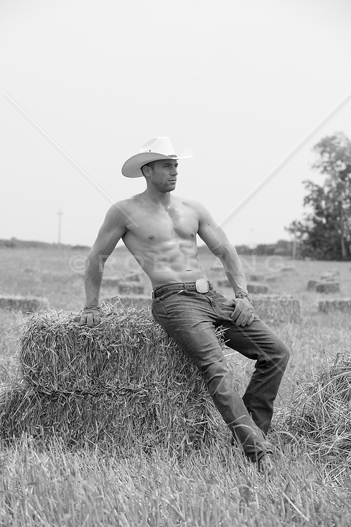 Shirtless muscular cowboy sitting on a bale of hay
