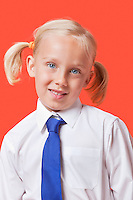 Portrait of a cute young girl in school uniform over blue background