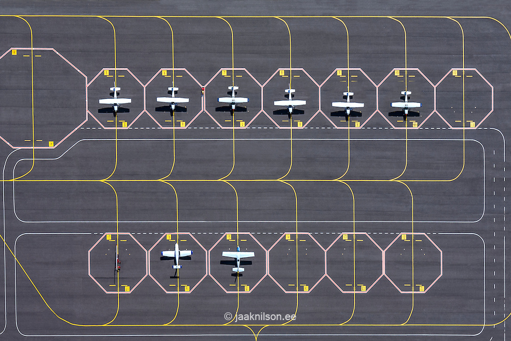 Divided parking lot with stripes and small airplanes. Tartu airport, Estonia