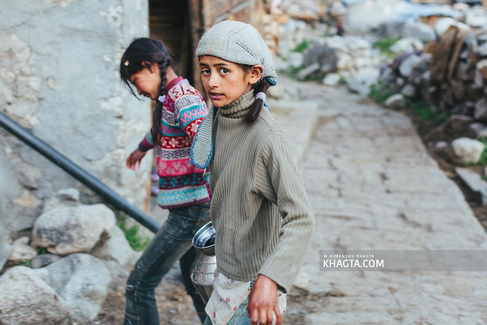 Two young girls carry water to their homes in Chitkul, Kinnaur