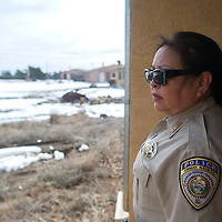 Ramah Police Officer Aileen Evensinvestigates an abandoned home showing signs of a break in in a small community in Pinehill January 23.
