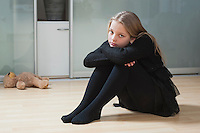 Portrait of an upset girl sitting on hardwood floor