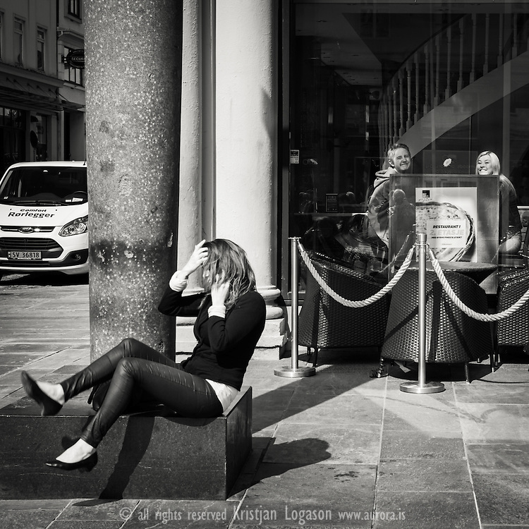 Woman sitting on a concrete a pillar on Torgalmenningen in central Bergan laughing and talking on the telephone while guest at nearby cafe give a big smile to the camera