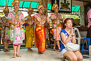 27 SEPTEMBER 2012 - BANGKOK, THAILAND: A woman prays while Thai classical dancers perform behind her at the Erawan Shrine in Bangkok. The woman paid for the dancers to help ensure her prayers would be heard. The Erawan Shrine is a Hindu shrine in Bangkok, Thailand, that houses a statue of Phra Phrom, the Thai representation of the Hindu creation god Brahma. A popular tourist attraction, it often features performances by resident Thai dance troupes, who are hired by worshippers in return for seeing their prayers at the shrine answered. The Erawan Shrine was built in 1956 as part of the government-owned Erawan Hotel to eliminate the bad karma believed caused by laying the foundations on the wrong date. The hotel's construction was delayed by a series of mishaps, including cost overruns, injuries to laborers, and the loss of a shipload of Italian marble intended for the building. Furthermore, the Ratchaprasong Intersection had once been used to put criminals on public display. An astrologer advised building the shrine to counter the negative influences. The Brahma statue was designed and built by the Department of Fine Arts and enshrined on 9 November 1956. The hotel's construction thereafter proceeded without further incident. In 1987, the hotel was demolished and the site used for the Grand Hyatt Erawan Hotel.     PHOTO BY JACK KURTZ