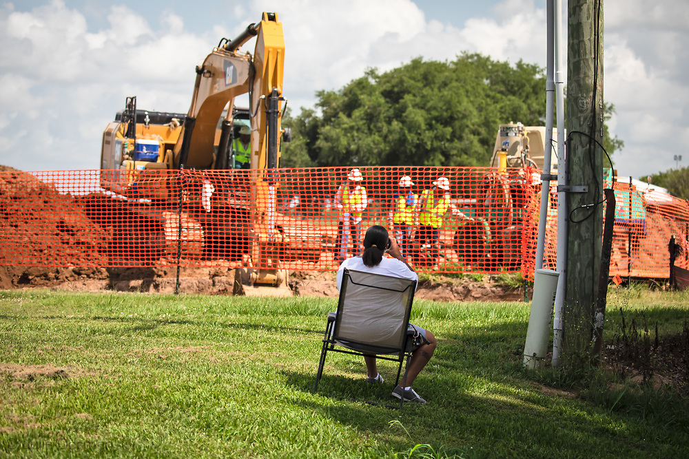 Melinda Tillies sitting in  a lawn chair on her front yard, using her phone to document the installation of the Bayou Bridge Pipeline next to her home in Youngsville, Louisiana. The pipeline was installed about 25 feet from her home on her neighbors land.  There are no federal rules about how close a pipeline can be built next to a home.