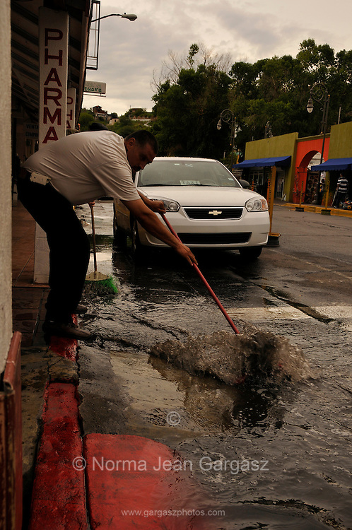 A merchant sweeps water from the street that was once busy with American tourists and shoppers after a monsoon storm in Nogales, Sonora, Mexico, across the border from Nogales, Arizona, USA.  Businesses in Nogales, Sonora, saw an economic decline after reports of cartel violence deterred tourists and shoppers from entering the country.