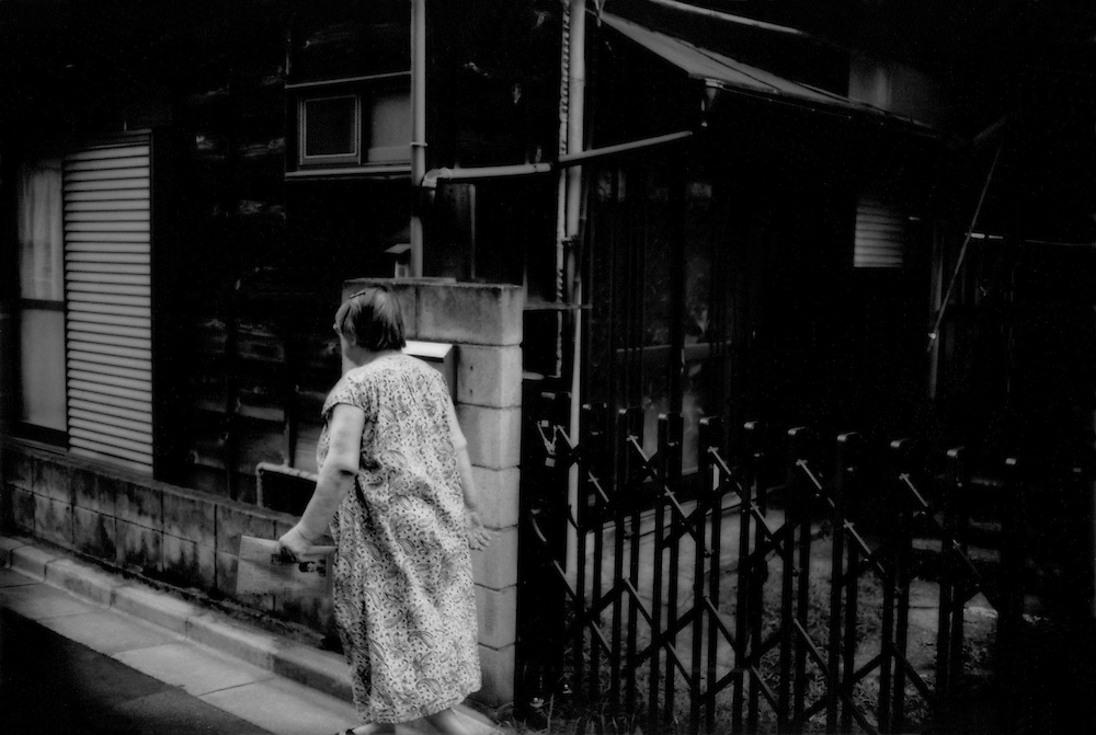 Privacy, Isolation / Elderly woman collects a newspaper in the afternoon and returns to her dark, wooden home in the style of the Showa Era (Emperor Hirohito's era) from the time immediate after the Second World War or before it, which has been  considered old and undesirable to Japanese families for a couple of decades.  It is by far the oldest house on the block and disshevelled.  Elderly people have died in Japan and not been found for extended periods of time in such dark houses not unlike this one, lacking gardens needing watering, accumulation of clutter or other obvious signs that someone might be seriously ill in the house.  Honmachii, Tokyo, Japan.