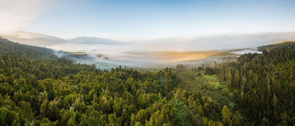 Stitched from 6 frames, this image captures early morning sunlight falling on the misty valley below Mt. Hercules, South Westland.