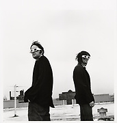 Two men standing on rooftop wearing white glasses.