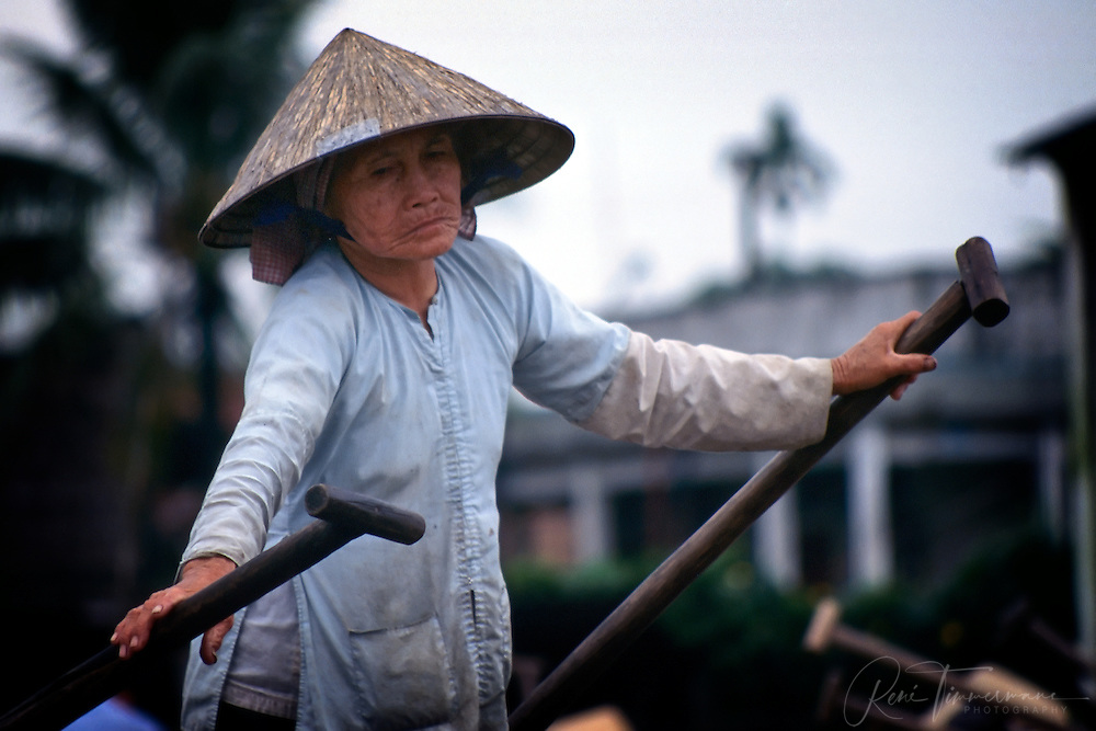 Woman rowing a boat in the Mekong Delta.