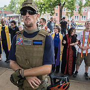 CHARLOTTESVILLE,VA-AUG12: Counter protestors hold hands and sing outside Emancipation Park during the Unite the Right Rally, while the self-proclaimed group, The Militia, stands guard. (Photo by Evelyn Hockstein/For The Washington Post)