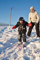 A three year old boy trying to ski for the first time. His mother helping him. Sunny weather and warm light from sun. Frá fyrstu skíðaferð Ara Carls í Ártúnsbrekku.