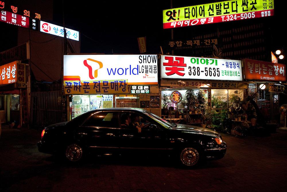 Luxus Auto vor Geschaeften und Restaurants im Hongdae Viertel. Dieses Gebiet vor der Hongik Universit&auml;t ist vor allem f&uuml;r das Nachtleben bekannt. Hier befinden sich sehr viele Discotheken, Bars und Restaurants.<br /> <br /> Luxery car in front of shops and restaurants at Hongdae quater. Hongdae area is an entertainment area and clubbing district in northwest Seoul, South Korea - close to the Hongik University.