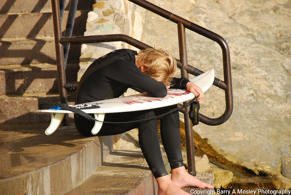 Young surfer with head down, disappointed in lack of waves for surfing. Photo by Nebraska Photographer Barry A Mosley.
