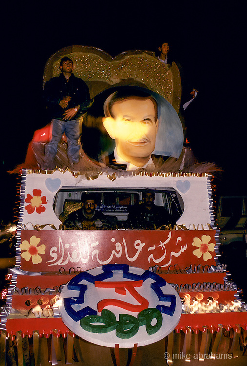 'PERSONALITY CULT OF ASSAD', MEN STANDING ON & DRIVING VEHICLE MADE INTO FLOAT WITH LARGE HEART SHAPED PHOTO OF ASSAD DURING THE REFURENDUM CAMPAIGN, DAMASCUS, DECEMBER 1991