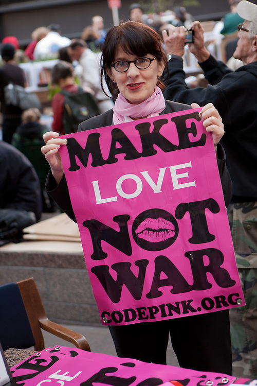 "A woman from Code Pink, a woman-initiated peace movement, holds a bright pink sign that reads ""Make love not war."""