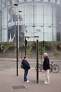 A tourist couple stand looking at both sides of a London visitors' map near the BFI Imax.