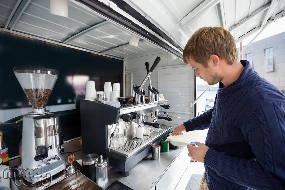 Young man working at mobile coffee shop