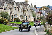 Vintage cars drive through Windrush village on a Veteran Car Club rally day, Gloucestershire, United Kingdom