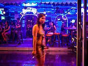 "12 JULY 2011 - BANGKOK, THAILAND: A woman walks past the ""Corner Bar"" during a rain storm on Soi Cowboy in Bangkok. Soi Cowboy is a ""red light"" district that is home to several brothels and ""short time"" hotels that charge by the hour for their rooms. Prostitution in Thailand is illegal, although in practice it is tolerated and partly regulated. Prostitution is practiced openly throughout the country. The number of prostitutes is difficult to determine, estimates vary widely. Since the Vietnam War, Thailand has gained international notoriety among travelers from many countries as a sex tourism destination. One estimate published in 2003 placed the trade at US$ 4.3 billion per year or about three percent of the Thai economy. It has been suggested that at least 10% of tourist dollars may be spent on the sex trade. According to a 2001 report by the World Health Organisation: ""There are between 150,000 and 200,000 sex workers (in Thailand).""  PHOTO BY JACK KURTZ"