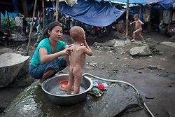 A Kachin woman wash her sons in Woi Chyai Internal Displacement People refugee camp in Laiza village close to the China border, Myanmar on August 5, 2012. According to KIO (Kachin Independence Organization) sources around 50000 Kachin people live as refugees in those camps.