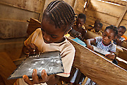 A girl solves a math problem on her slate during class at the Podio primary school in the village of Podio, Bas-Sassandra region, Cote d'Ivoire on Friday March 2, 2012.