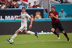July 31, 2018 - Miami Gardens, Florida, USA - Real Madrid C.F. forward Gareth Bale (11) drives the ball chased by Manchester United F.C. defender Luke Shaw (23) during an International Champions Cup match between Real Madrid C.F. and Manchester United F.C. at the Hard Rock Stadium in Miami Gardens, Florida. Manchester United F.C. won the game 2-1. (Credit Image: © Mario Houben via ZUMA Wire)