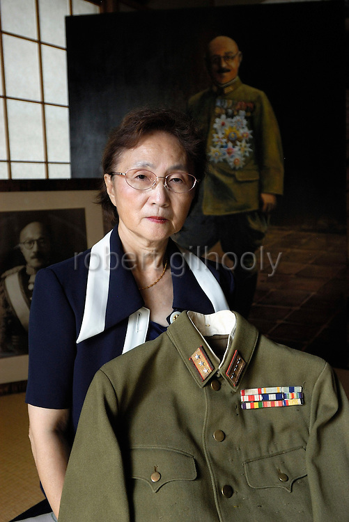 """Yuko Tojo, granddaughter of Japan's wartime leader, General Hideki Tojo, poses with her grandfather's uniform at her home in Tokyo, Japan in 2005. Gen. Tojo - who ordered the attack on Pearl Harbor -- was charged and hanged as a war criminal after World War II when Yuko was just 6, and though she remembers little of her grandfather she still regards him as a hero. """"Japan did not fight a war of aggression but in self-defense,"""" says Ms. Tojo, widely seen as a leading figurehead in a recent surge in nationalism in Japan and who unsuccessfully ran for a seat in Japan's House of Councilors in 2007. """"Schoolchildren are told what evil things our country and their ancestors did during the war and this has led to a lack of pride in the Japanese people. This is wrong. We must reinstall a sense of pride and confidence in our children to make our country strong again."""""""