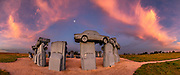 """Carhenge sunrise. Carhenge replicates England's Stonehenge using vintage American automobiles, near Alliance, Nebraska, in the High Plains region, USA. After studying Stonehenge in England, years later, Jim Reinders recreated the physical size and placement of Stonehenge's standing stones in summer 1987, helped by 35 family members. Reinders said, """"It took a lot of blood, sweat, and beers."""" Carhenge was built as a memorial to Reinders' father. 39 automobiles were arranged in the same proportions as Stonehenge with the circle measuring a slightly smaller 96 feet (29m) in diameter. Some autos are held upright in pits five feet deep, trunk end down, while other cars are placed to form the arches and welded in place. All are covered with gray spray paint. The heel stone is a 1962 Cadillac. Reinders donated Carhenge to the Friends of Carhenge, who gifted it to the Citizens of Alliance in 2013. Additional sculptures have been erected in the Car Art Reserve, where Reinders' """"Ford Seasons"""" is comprised of four Fords, inspired by Vivaldi's Four Seasons. Also, 29-year-old Canadian Geoff Sandhurst sculpted a spawning salmon. This image was stitched from multiple overlapping photos."""
