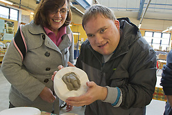 Visually impaired people with carers on outing to Denby Pottery.  Moulding clay into frog shape.