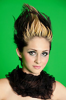 Portrait of beautiful young woman wearing scarf with spiked hair over green background