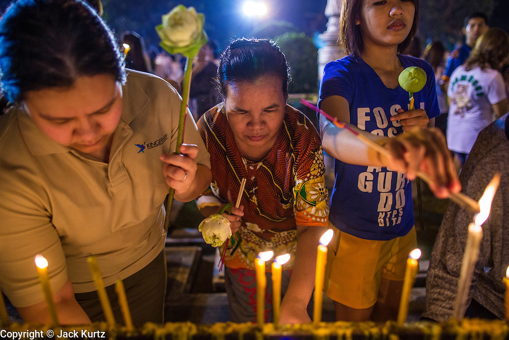 "25 FEBRUARY 2013 - BANGKOK, THAILAND:  Thais light candles and pray at Wat Benchamabophit Dusitvanaram (popularly known as either Wat Bencha or the Marble Temple) on Makha Bucha Day. Thais visit temples throughout the Kingdom on Makha Bucha Day to make merit and participate in candle light processions around the temples. Makha Bucha is a Buddhist holiday celebrated in Myanmar (Burma), Thailand, Cambodia and Laos on the full moon day of the third lunar month (February 25 in 2013). The third lunar month is known in Thai is Makha. Bucha is a Thai word meaning ""to venerate"" or ""to honor"". Makha Bucha Day is for the veneration of Buddha and his teachings on the full moon day of the third lunar month. Makha Bucha Day marks the day that 1,250 Arahata spontaneously came to see the Buddha. The Buddha in turn laid down the principles his teachings. In Thailand, this teaching has been dubbed the 'Heart of Buddhism'.     PHOTO BY JACK KURTZ"