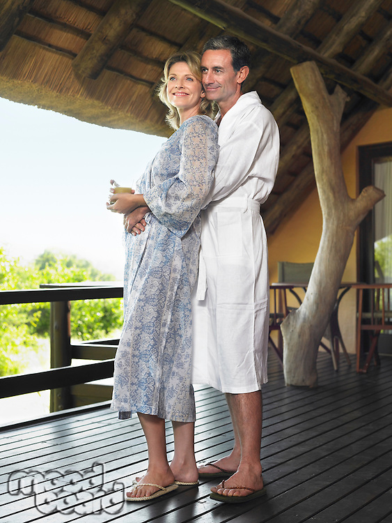 Adult couple in bathrobes embracing on terrace