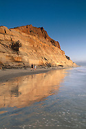Couple walking on sand below steep rugged golden coastal cliffs, Torrey Pines State Beach, San Diego, California