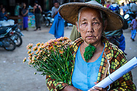 BAGAN, MYANMAR - CIRCA DECEMBER 2013: Old Burmese woman walking in the streets of  Nyaung U market close to Bagan in Myanmar with some flowers.