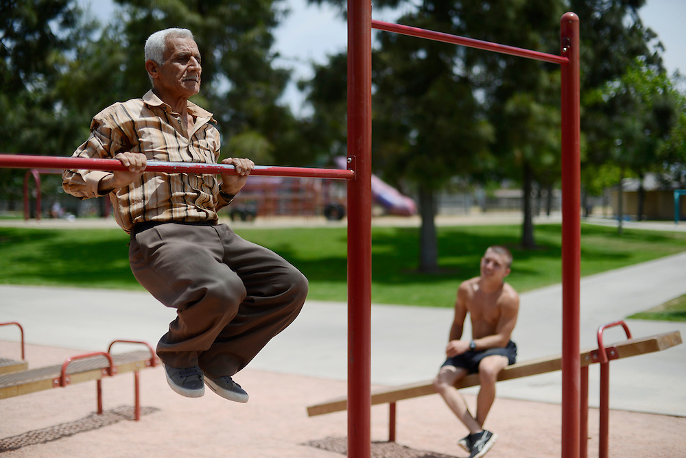 Antoun, 70, was a well-known weightlifting and boxing champion in Iraq in the 1970s. He's still in excellent physical condition. Since coming to the States seven months ago with his grown children and grand children, he does not have much to do. He spends his days going to the park to exercise and talk with other Iraqi refugees. Brett Wilson, 20, is from El Cajon. He just enlisted in the US Army and is waiting for his induction and basic training boot camp to start at Fort Benning, GA. He wants to be part of the elite Army Rangers Corps and is training to be ready for the physical demands. Despite the 50 years that separate them in age, the lack of a common language and the history of conflict between their two countries, Antoun and Brett have become friends and work out together on a daily basis in the park. Antoun instructs Brett on his training form and technique and Brett provides some camaraderie and purpose for Antoun's daily routine. El Cajon, CA, USA. 02/05/2013.