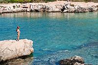 """Bagnanti a Porto Selvaggio - Reportage fotografico di Alessandro Caniglia, Alessandro De Matteis e Dario Luceri - Il Parco Naturale Regionale di Porto Selvaggio è situato lungo la costa ionica e ricade nel comune di Nardò (Lecce). Definito come """"area di notevole interesse pubblico"""" già nel 1939, è stato effettivamente istituito come Parco nel 2004. I suoi limiti sono compresi tra la baia di Frascone (a nord) e la Torre dell'Alto (a sud). Ha una estensione complessiva di circa 1000 ettari.Porto Selvaggio è una delle zone tra le più incontaminate del litorale Ionico, con un paesaggio caratterizzato da una pineta di ca. 300 ettari e da una macchia mediterranea ricca di acacee e ginestre..Lungo la costa sono presenti molte cavità carsiche, con varie insenature, grotte sommerse.Per gli amanti della natura il paesaggio è estremamente suggestivo in ogni stagione: molto silenzioso e rilassante in autunno, inverno e primavera, ricco di colori e festoso in estate, con il canto delle cicale che accompagna i visitatori lungo i sentieri e di tratti di scogliera che portano fino alla spiaggia. Il mare limpido e azzurro, con un fondale ricco di flora e fauna marina, è spesso meta di numerosi subacquei."""