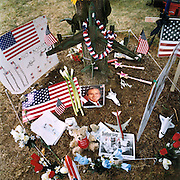 "Patriotic Americana - After 9/11. American icons dislayed beneath a tree near the Pentagon. In the week after the September 11th attacks, America sought to express their anger and patriotic unity. A smiling portrait of President Bush is surrounded by icons of American achievement, including a garlanded B52 bomber, placed as a makeshift memorial overlooking the charred Pentagon building, Washington DC. ""President Bush is a great Christian.. the angels are looking after him and America."" - As quoted from a Washington citizen."