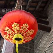 A Red traditional red lanter hang from a wooden roof of a walled city in Sha Tin.