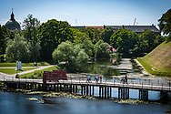 A view of the river with people crossing the bridge at Kastellet in Copenhagen.