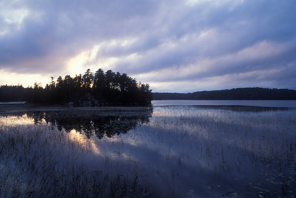 Canada, Ontario, Nestor Falls, Setting sun over islands in Lake of the Woods on autumn evening