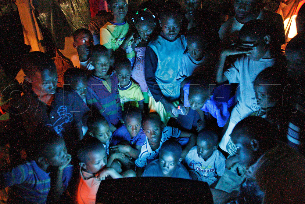 Children watch Jerry La Grenade, 12, at center,  play video games at a tent city for earthquake survivors at St. Pierre Park in Petion-Ville on March 3. 2010...