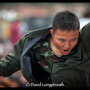 A Sak Yant devotee works himself into a frenzy during festivities at the Wat Bang Phra tattoo festival in Nakhon Chai Si province on the outskirts of Bangkok, Thailand.