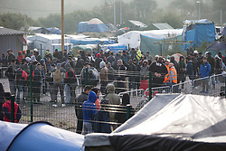 © Licensed to London News Pictures . 24/10/2016 . Calais , France . People queue to leave the Jungle migrant camp in Calais , Northern France , with their parents , on the day of a planned eviction and start of the destruction of the camp . Photo credit: Joel Goodman/LNP