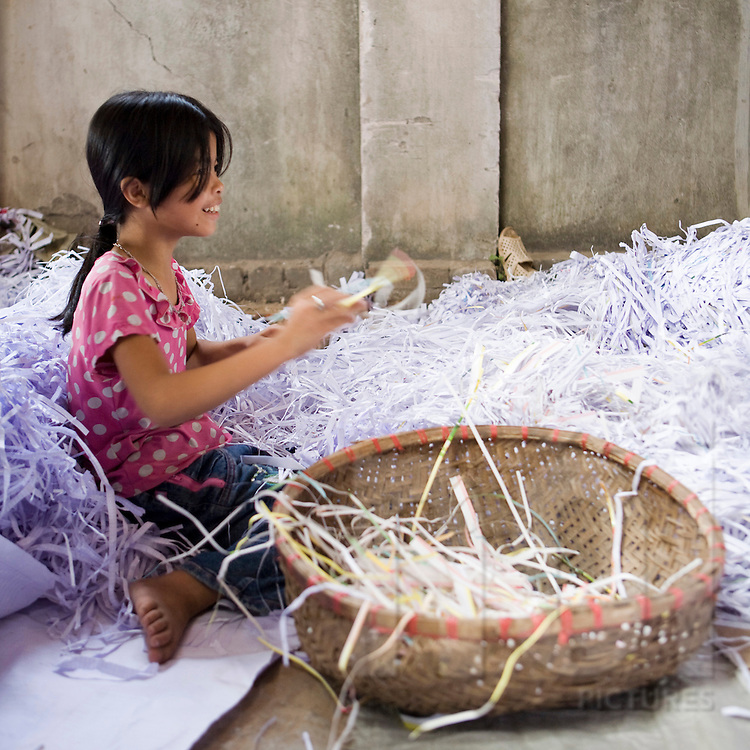 Workshop of recycling paper in the village of Cham Khe close from Hanoi. Child working in a paper workshop