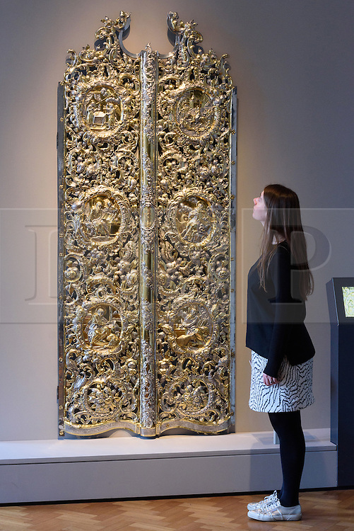© Licensed to London News Pictures. 15/11/2016. Museum staff member views a pair of Kiev Monastery Gates (about 1784).  These magnificent silver gilt and iron gates were commissioned by Catherine the Great of Russia and made for an Orthodox church in a monastery in Kiev.  The piece is showing as part of the r-opening of the V & A's Rosalinde and Arthur Gilbert Galleries. London, UK. Photo credit: Ray Tang/LNP
