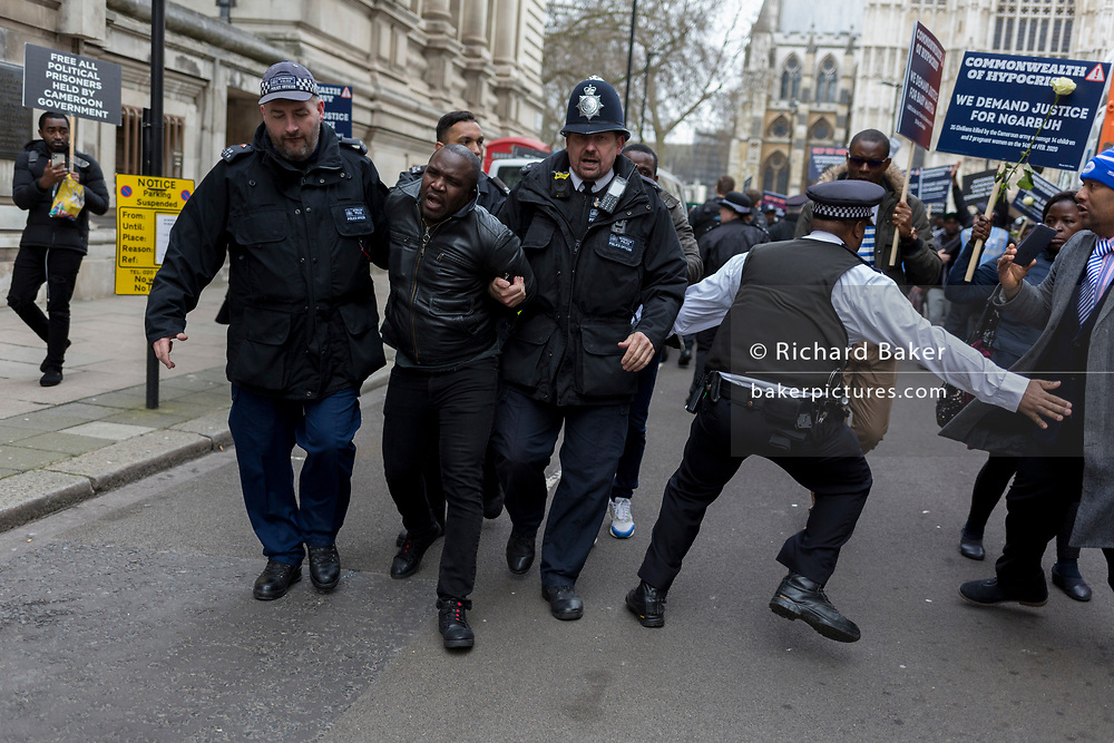 Pro-Democracy protesters with a Free Southern Cameroon group are tackled by Metropolitan police officers after dashing out from behind barriers outside Westminster Abbey during the Commonwealth Day service lead by the Queen and including members of the British royal family and Commonwealth ambassadors and dignitaries. They are holding placards saying Free President Ayuktabe Julius' (an Ambazonian separatist leader) and 'Justice for Babanki' (referring to allegations of soldier killings on villagers), on 9th March 2020, in London, England. At this, their last royal duty before stepping down for private careers, Prince Harry and his wife Meghan, the Duke and Duchess of Sussex will remain president and vice-president of the Queen's Commonwealth Trust, respectively.