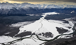 "This aerial photograph of a portion of the ""Council Grounds"" is the primary area where bald eagles gather on the Chilkat River in the Alaska Chilkat Bald Eagle Preserve near Haines, Alaska. Bald eagles come to the alluvial delta area at the confluence of the Tsirku (center) and Chilkat (left to right) Rivers because of the availability of spawned-out salmon and open waters in late fall and early winter. The open water is due to a deep accumulation of gravel and sand that acts as a large water reservoir whose water temperature remains 10 to 20 degrees warmer than the surrounding water temperature. This warmer water seeps into the Chilkat River, keeping a five mile stretch of the river from freezing. Photographers come to the Chilkat River in November and December to photograph one of the largest gatherings of bald eagles in the world. In 1982, the 48,000 acre area was designated as the Alaska Chilkat Bald Eagle Preserve. In the background are the mountains that make of the Takhin Ridge and Takhinsha Mountains. Chilkat Lake is pictured on the left, below the mountains."