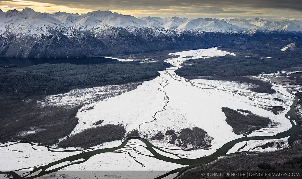 """This aerial photograph of a portion of the """"Council Grounds"""" is the primary area where bald eagles gather on the Chilkat River in the Alaska Chilkat Bald Eagle Preserve near Haines, Alaska. Bald eagles come to the alluvial delta area at the confluence of the Tsirku (center) and Chilkat (left to right) Rivers because of the availability of spawned-out salmon and open waters in late fall and early winter. The open water is due to a deep accumulation of gravel and sand that acts as a large water reservoir whose water temperature remains 10 to 20 degrees warmer than the surrounding water temperature. This warmer water seeps into the Chilkat River, keeping a five mile stretch of the river from freezing. Photographers come to the Chilkat River in November and December to photograph one of the largest gatherings of bald eagles in the world. In 1982, the 48,000 acre area was designated as the Alaska Chilkat Bald Eagle Preserve. In the background are the mountains that make of the Takhin Ridge and Takhinsha Mountains. Chilkat Lake is pictured on the left, below the mountains."""