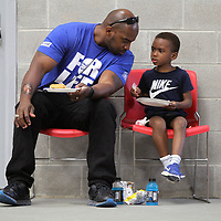 """Johnny Mickell, of Tupelo, leans over to talk with his son, Johnny Mickell Jr., as they eat their BBQ dinner inside the Theron Nichols Community Center during the """"Father Son Fun Day"""" in Tupelo Thursday night."""